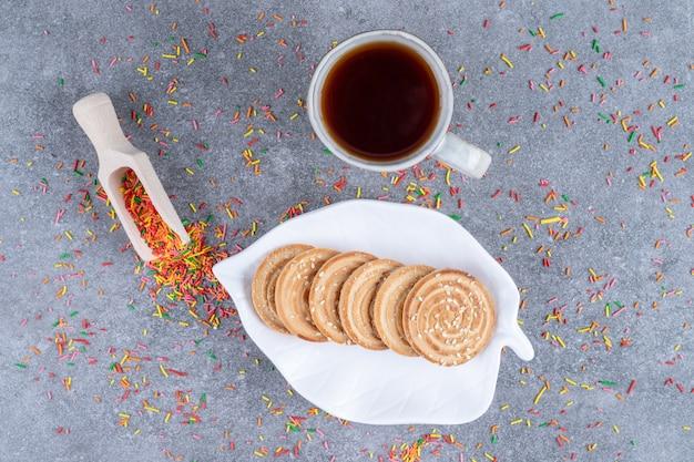 Un piatto di biscotti, una paletta con una spruzzata di caramelle e una tazza di tè