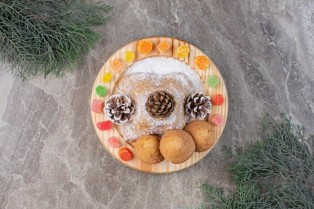 Блюдо декорировано мармеладом, печеньем, сосновыми шишками и ванильной пудрой на мраморе.