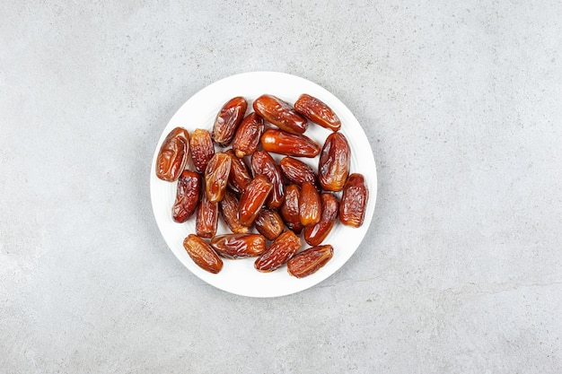 A platter of fresh dates on marble surface