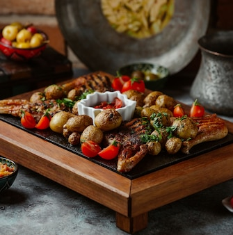 A platter of grilled beef, potatoes and vegetables on a stone table