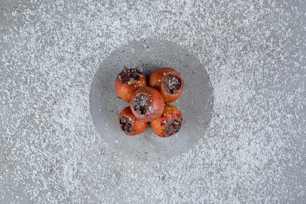 Piatto di cachi su polvere di cocco sparsa sulla superficie di marmo