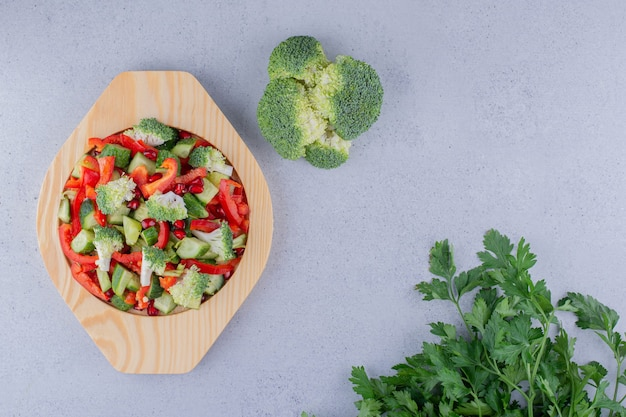 Блюдо салата с пучками брокколи и петрушки на мраморном фоне.