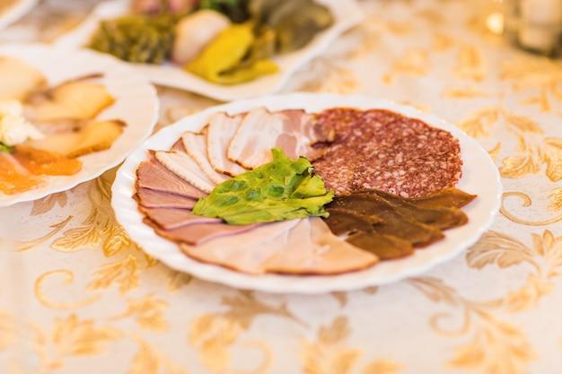 얇게 썬 햄, 살라미, 고기를 야채 장식과 함께 축제 테이블에 플래터