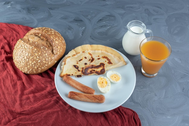 Platter of pancake, sausages and slices of boiled egg next to milk, juice and bread on marble surface.