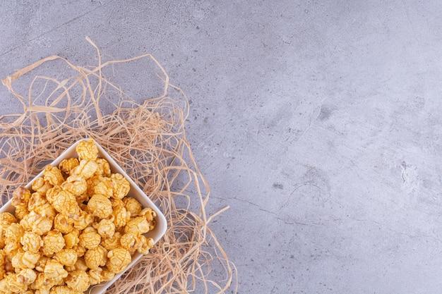 Piatto su un mucchio di paglia riempito con un mucchio di caramelle popcorn su sfondo marmo. foto di alta qualità