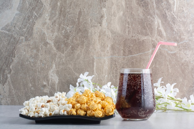 A platter of popcorn, a glass of cola and a bunch of flowers on marble.
