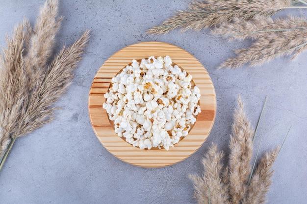 Piatto di popcorn circondato da aghi secchi sulla superficie in marmo