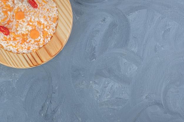 Piatto di riso cotto con carote, guarnito con fette di pepe su fondo di marmo.