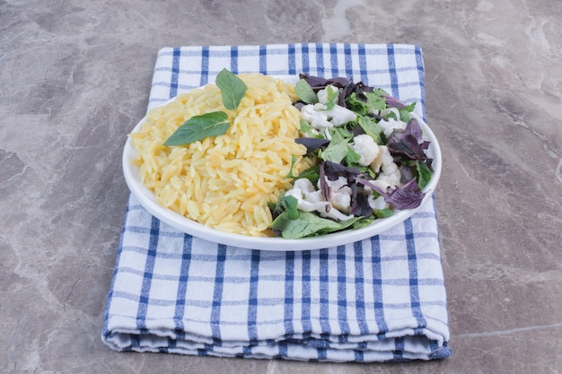 Platter of rice pilau accompanied by a salad mix of amaranth, basil and cauliflower on folded towel on marble surface