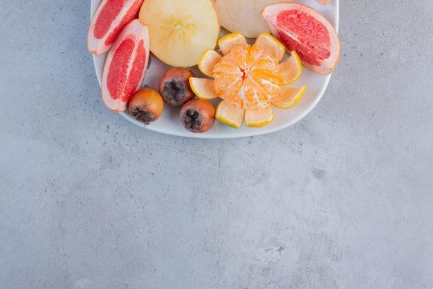 Un piatto di pompelmi a fette, pere e un mandarino sbucciato su fondo di marmo.