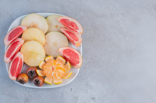 A platter of sliced grapefruits, pears and a peeled tangerine on marble background.