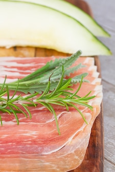 Platter of spanish cured pork ham jamon close up with melon and rosemary