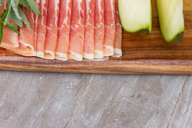 Platter of spanish cured pork ham jamon with melon on gray table border