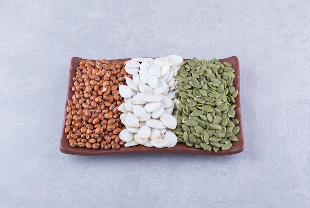 Piatto rifornito con fagioli rossi, semi di zucca bianchi e pepita su superficie di marmo