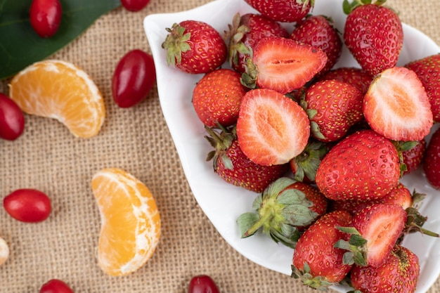 A platter of strawberries and a handful of tangerine slices and hips on textile background. high quality photo
