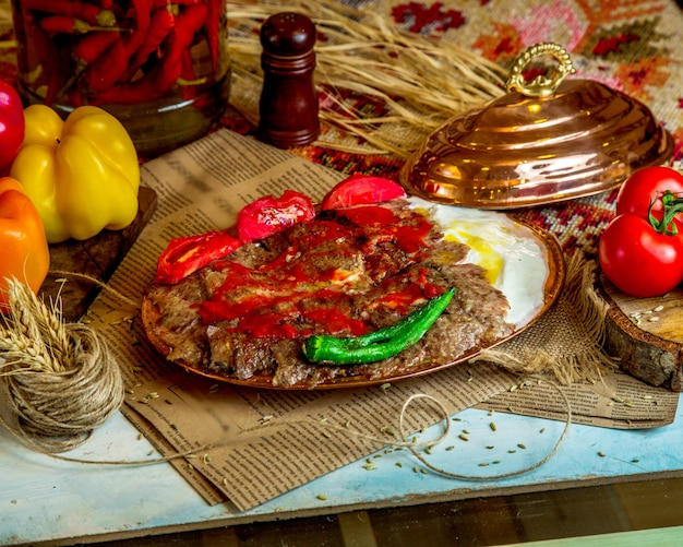 A platter of turkish lamb kebab served with yogurt grilled tomato and pepper