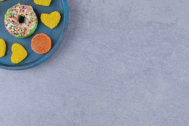 Блюдо с маленьким пончиком и различными мармеладами на мраморной поверхности