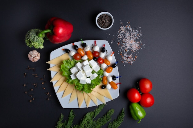 Platter with cheese, tomatoes and olives, on black with tomatoes, dill, garlic, green pepper and broccoli