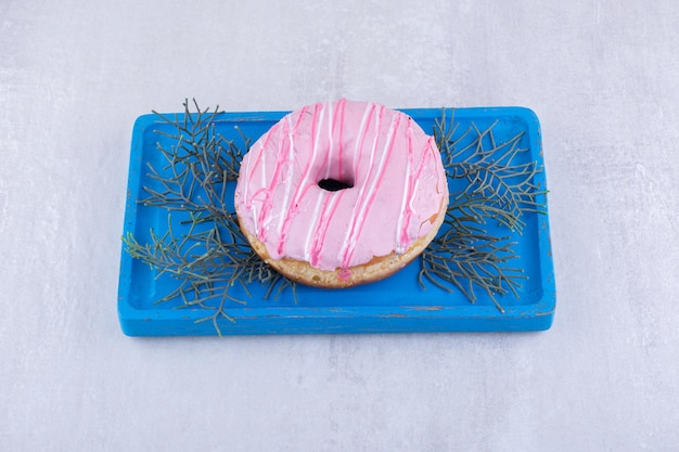 Platter with a glazed donut placed on pine tree leaves on white surface