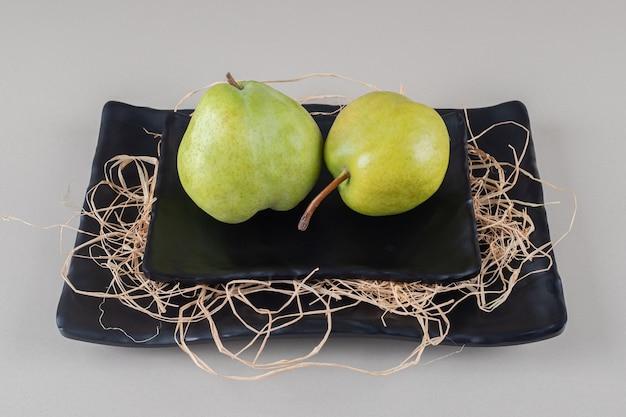 Un piatto di pere su un piatto di paglia su marmo
