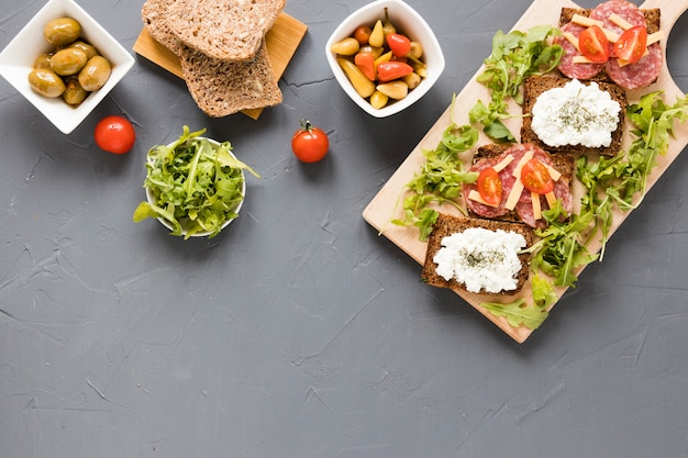 Platter with sandwiches and vegetables with copy space