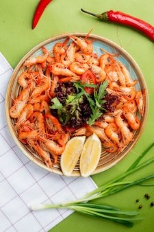 A platter with shrimps and topped with herbs