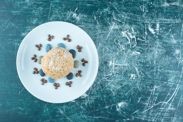 Un piatto con torta di scoiattolo, rocce di caramelle e chicchi di caffè sul blu.