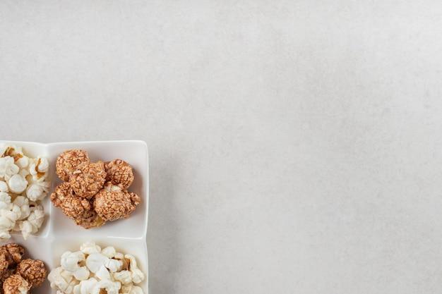 大理石のテーブルの上に、塩味のポップコーンとキャンディーのポップコーンをそれぞれ2つずつ盛り合わせた大皿。