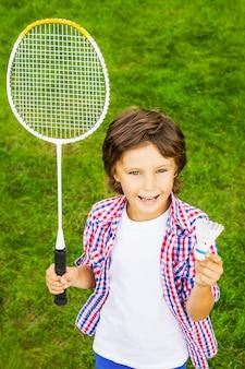 バドミントンをする?緑の芝生の上に立っている間バドミントンラケットとシャトルコックを保持している幸せな少年の上面図