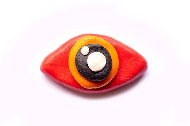 Тесто для лепки глаз на белом фоне. значок глаз. пластилин из глины ручной работы