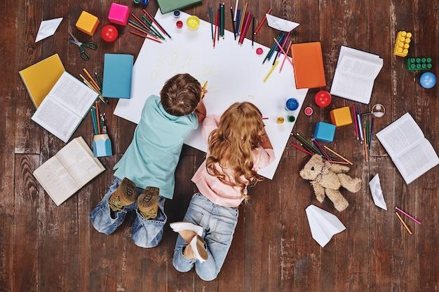 Игра - это работа детей детства, лежащих рядом с книгами и игрушками во время рисования.