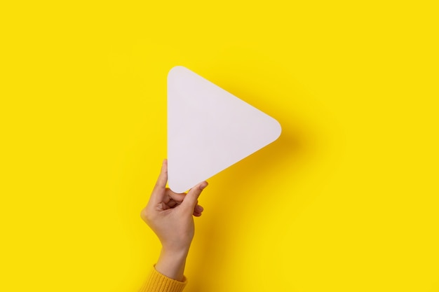 Play symbol in hand over yellow background, multimedia concept