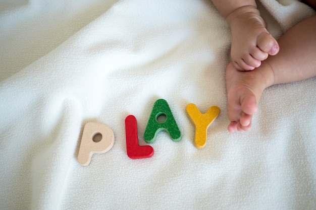 Play text wooden word on blanket with foot kid and copy space background