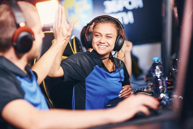 두 명의 젊은 행복한 전문 사이버 스포츠 게이머를 하이파이브하기 위해 플레이하십시오.