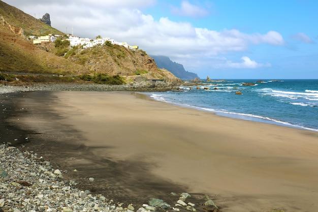 Пляж плайя-де-альмасига с деревней на холме, тенерифе, испания