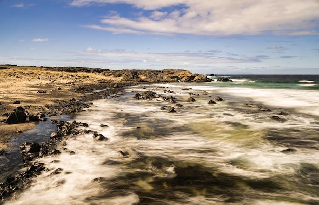 Пляж плайя-де-лас-аренас-бланкас, белый песок и вулканические породы, фотография с большой выдержкой, голубое небо и белые облака, атлантический океан, ла-фронтера, эль йерро, канарские острова, испания