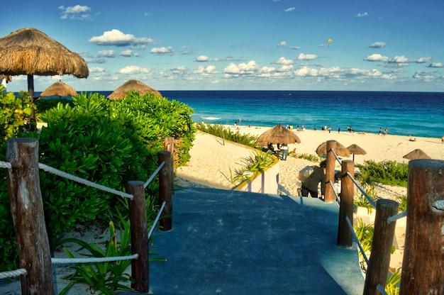 Красивый пляж в канкуне, мексика - playa delfines. пляж кинтана-роо в солнечный день. прекрасный вид на карибское море с туристами, наслаждающимися их каникулами