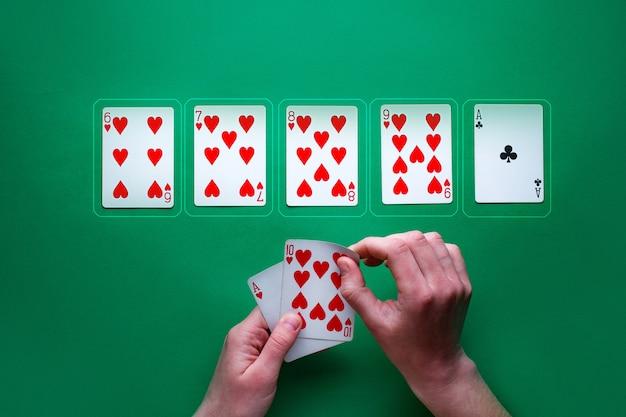 Игрок за столом играет и показывает карты в покер. выигрышная комбинация. игромания. техасский холдем