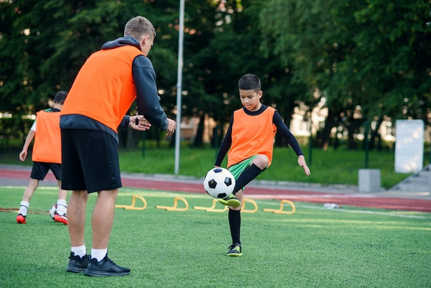 Player in football uniform working out the kicking ball with coach on stadium