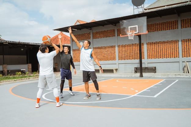 プレーヤーはボールを持ってフープに3ポイントシュートします