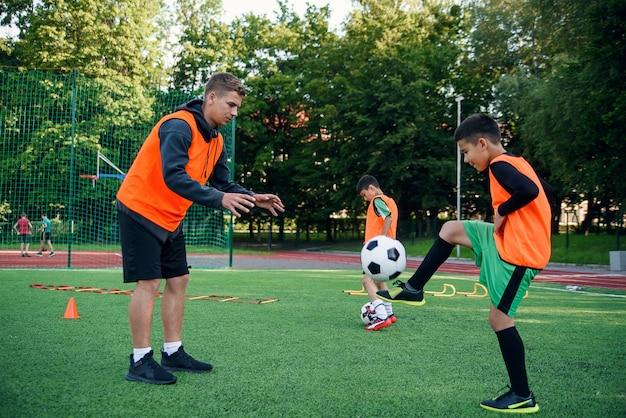 Игрок в футбольной форме тренирует удар ногой с тренером на стадионе