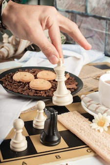 Player playing chess on a pastry table