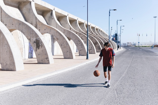 Player practicing basketball on road in city