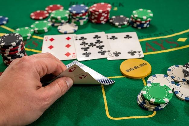 플레이어는 카지노 wirh 칩의 녹색 테이블에 두 개의 플레이 카드 에이스를 보여줍니다. 도박