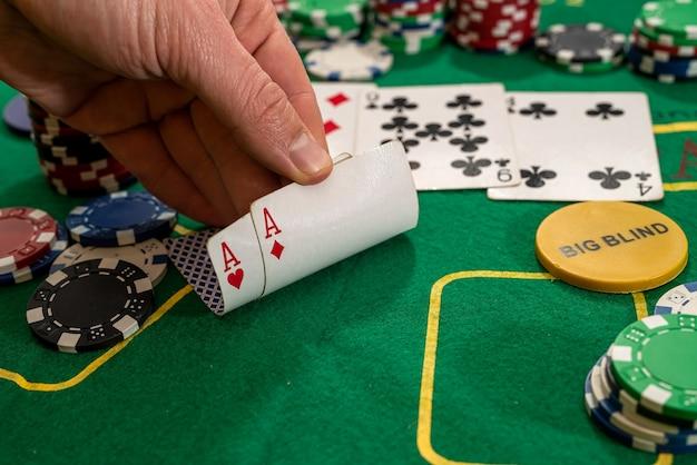 플레이어는 칩이있는 카지노의 녹색 테이블에 두 개의 플레이 카드 에이스를 보여줍니다.
