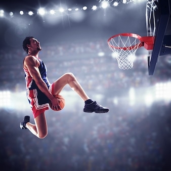 Player throws the ball in the basket in the stadium full of spectators