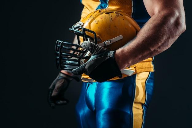 手にアメリカンフットボールのヘルメットを持つプレーヤー