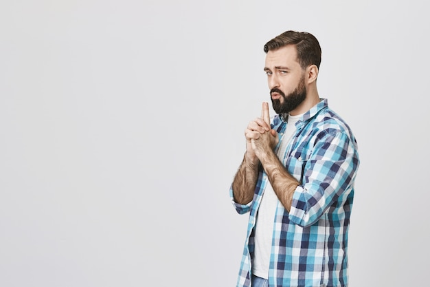 Playful adult bearded man acting like secret agent, blowing at finger gun