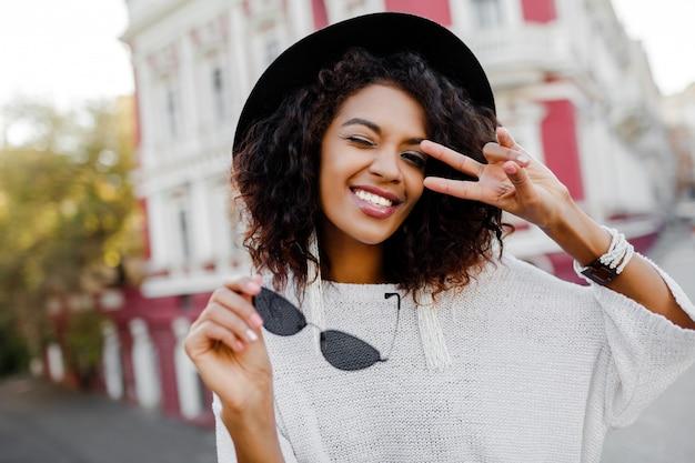 Игривая африканская леди в модном наряде наслаждается хорошим днем на фотосессии. идеальная откровенная улыбка, белые зубы. черная шляпа.
