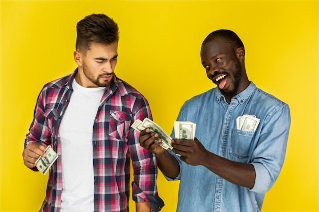 Playful african man joking with beautiful european man while the holding money